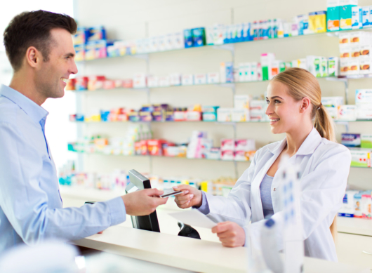 Pharmacist and client at pharmacy, smiling