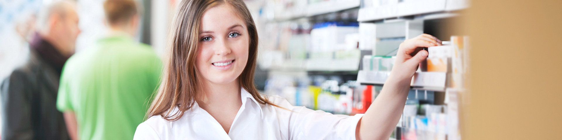 Portrait of female pharmacist holding tablet PC standing by the shelf at drugstore