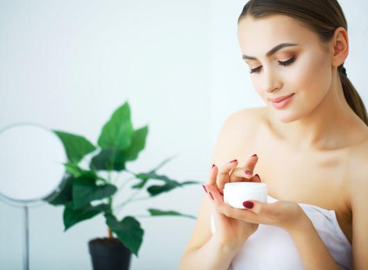 A beautiful woman using a skin care product, moisturizer or loti